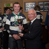 The Corinthians captain is presented with the Senior Club Sevens trophy by the Michael Cunningham of the IRFU