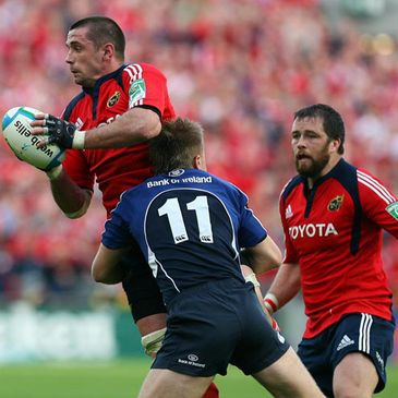 Munster flanker Alan Quinlan is tackled by Leinster's Luke Fitzgerald