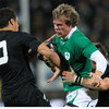 Ireland winger Andrew Trimble grimaces as he tries to break away from Dan Carter and Richie McCaw