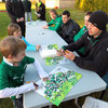 Two young Ireland fans look on as the players chat to them and sign posters