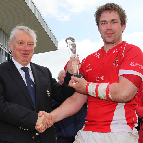 The IRFU's Nicky Comyn presents the trophy to Cashel's Brendan O'Connor