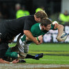 Ireland captain Brian O'Driscoll tries to slip a one-handed pass away as the New Zealand cover gets across