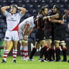 Ulster replacement prop Bryan Young shows his disappointment as the Edinburgh players celebrate their two-try victory