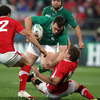 Cian Healy attempts to barge past Wales out-half Rhys Priestland as Jamie Roberts moves in to make a tackle