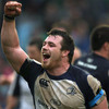 Leinster prop Cian Healy raises his arm in triumph as the province's players and supporters celebrate the win
