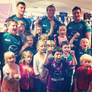 The Connacht players are pictured with some young fans