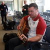 Damien Varley got a lend of a guitar from a local woman and showed off his musical skills as the players waited to board the plane to Dunedin
