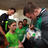 These green-clad youngsters patiently wait as Damien Varley signs some mini rugby balls and hands out IRFU keyrings