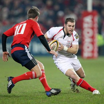 Ulster centre Darren Cave takes on Munster's Ronan O'Gara