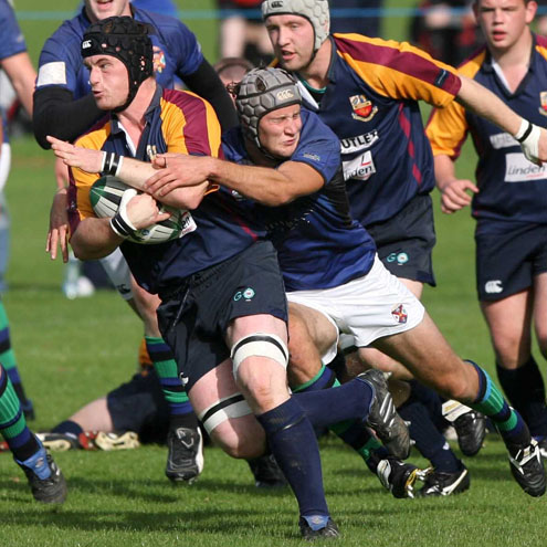 Banbridge flanker Darren Cochrane is tackled by Gareth Hooks of Queen's