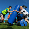 The squad's masseur Dave Revins holds a tackle bag for Jonathan Sexton during a training drill in Takapuna