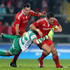Treviso winger Benjamin de Jager tries to bring down Munster's David Wallace, who has James Coughlan in support