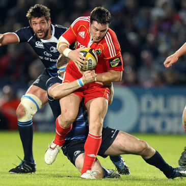 Munster flanker David Wallace is tackled by Leinster's Jamie Heaslip