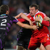 As the sides scrap for possession, Munster hooker Denis Fogarty tries to fend off Ospreys centre Andrew Bishop
