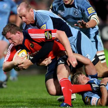 Munster full-back Denis Hurley is tackled by Cardiff's Gareth Thomas