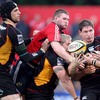 Munster flanker Donnacha Ryan competes for possession with Adam Jones of the Dragons