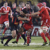 Munster winger Doug Howlett protects the ball as Dragons flanker Gavin Thomas rushes in to tackle him