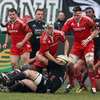 Tackled by Aironi's Tommaso d'Apice, Munster scrum half Duncan Williams looks to pass to a team-mate