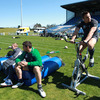 Keith Earls and Denis Leamy sit on some tackle bags watching their colleagues train, with Tommy Bowe, who suffered a bump on his calf against Australia, pedalling away on an exercise bike