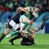 Challenged by two American players, Eoin Reddan keeps a tight hold of the ball as he tries to vault over one of them