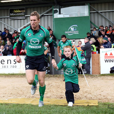 Gavin Duffy and a team mascot run out in front of the Clan Terrace