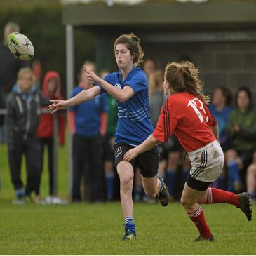 Ellen Taite of Leinster gets the ball away under pressure from Ciara McLoughlin