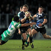 Leinster's reserve out-half Ian Madigan protects the ball as he is tackled by Treviso's Joe Maddock