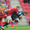 Ian Madigan, who scored 15 points for the visitors, is pictured being tackled by Scarlets flanker Josh Turnbull