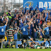 The Leinster players and supporters raise their arms in celebration as Isa Nacewa crashes over the try-line at the Havelock Square end of the ground