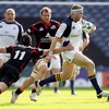 Edinburgh winger Simon Webster stretches as he tries to stop the progress of Leinster's Jamie Heaslip