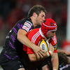 Munster centre Johne Murphy, making his third league appearance, is tackled by the Ospreys' Andrew Bishop