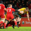 Australia centre Pat McCabe is brought to ground by Munster's Johne Murphy during the Thomond Park tussle