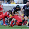 Ospreys number 8 Jonathan Thomas is tackled by Munster's Felix Jones and Conor Murray during the first half