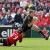 Ospreys centre Andrew Bishop is stopped in his tracks by Munster's Keith Earls