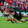 Munster centre Keith Earls is hauled down by Ospreys wide man Ashley Beck