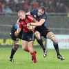 Munster full-back Keith Earls tries to power through two tackles in the wet conditions in Limerick