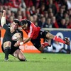New Zealand's Corey Flynn is hit hard by Munster centre Lifeimi Mafi