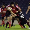 Edinburgh's Phil Godman tries to halt the progress of Munster centre Lifeimi Mafi