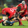 Munster's Johne Murphy, Doug Howlett and Duncan Williams swarm over Australia winger Luke Morahan
