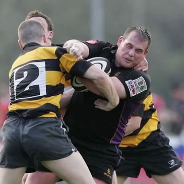 Instonians' Chris Schofield is tackled by Steve Corry of Young Munster
