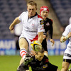 Ulster winger Mark McCrea puts boot to ball, despite the best efforts of Edinburgh's busy scrum half Greig Laidlaw