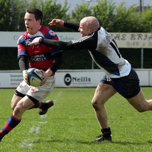 Clontarf out-half Martin Dufficy tries to get away from Cork Con's Cronan Healy