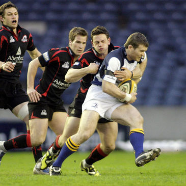 Leinster centre Gordon D'Arcy is tackled by Edinburgh's Nick De Luca