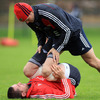 Paul Darbyshire, Munster's head of strength and conditioning, assists back rower Alan Quinlan through some stretches