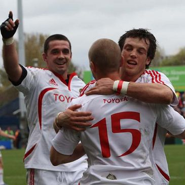 Alan Quinlan and Ian Dowling celebrate with try scorer Paul Warwick
