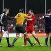 Assistant referee David Wilkinson has to intervene as Australia lock Rob Simmons and Munster's Peter O'Mahony clash off the ball