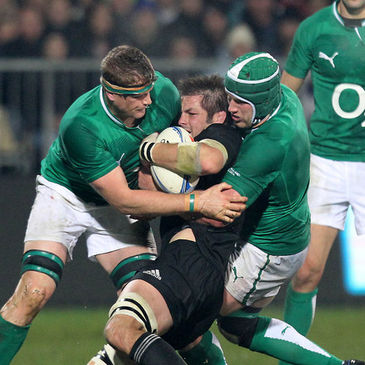 Richie McCaw is tackled by Jamie Heaslip and Sean O'Brien