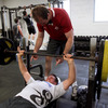 Ronan O'Gara gets stuck into his weights programme, with fellow back Geordan Murphy spotting for him