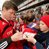 A young Munster fan patiently waits as Ronan O'Gara signs his programme