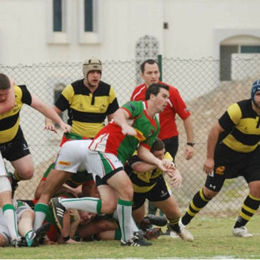 Scrum half Ross O'Loughlin gets his pass away for the Muscat team